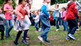 MOSCOW RAMESKOYE-06.07.2019: Animators entertain children dancing at a children`s party. Children dance in the yard to. Family and Friends Dancing together at stock video