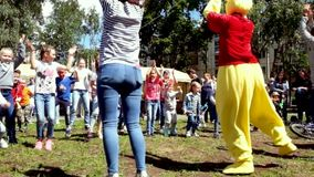 MOSCOW RAMESKOYE-06.07.2019: Animators entertain children dancing at a children`s party. Children dance in the yard to. Family and Friends Dancing together at stock footage