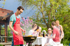 Family and friends having bbq at garden party. Men in the foreground on grill, in background people drinking and eating Royalty Free Stock Photos