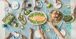 Family or friends having seafood summer dinner. Family or friends summer party or seafood dinner. Flat-lay of group of mutinational people with different skin stock images