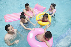 Family and friends playing in the water at the pool with inflatable tubes Stock Photography