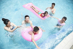 Family and friends playing in the water at the pool with inflatable tubes Royalty Free Stock Images