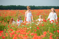 Family with friends in red poppy field Stock Photography