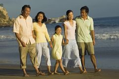 Family And Friends Walking On Beach Stock Photo