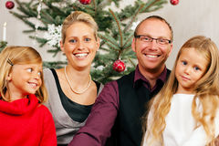 Family in front of Christmas tree Royalty Free Stock Image