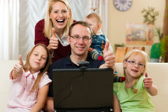 Family in front of computer having video conferenc. Young family in front of computer with camera Royalty Free Stock Images