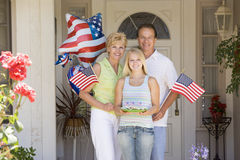 Family at front door on fourth of July with flags royalty free stock photography