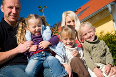 Family in front of home. A young family with three children in front of their new home sitting in the sun Stock Images
