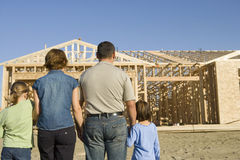 Family In Front Of Incomplete House. Rear view of family standing in front of incomplete house royalty free stock photography