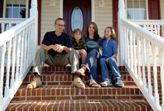 Family on front porch. A family of four sitting on the steps of a front porch. Home owners Royalty Free Stock Images