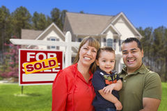 Family in Front of Sold Real Estate Sign and House Royalty Free Stock Image