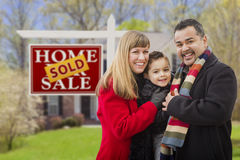 Family in Front of Sold Real Estate Sign and House Stock Image