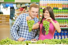 Family at fruit food shopping in supermarket. Young family couple choosing bio food grape fruit in vegetable supermarket during weekly shopping Stock Photography