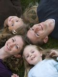Family Fun. Happy smiling family, lying on the grass with heads together Royalty Free Stock Photo