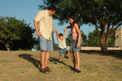 Family Fun. Happy american family, a diverse one, outside enjoying nature and spending time together. Family at the park. Little boy being picked up and swung by stock photo
