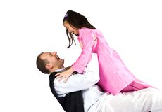 Family fun. A little girl throwing herself onto her daddy in a game of catch Stock Images