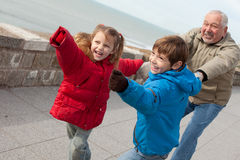 Family fun. Cute kids playing with their grandfather outdoors Stock Photography
