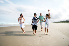 Family fun. A caucasian white family of four having fun together and running on the beach
