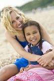 Family Fun. A beautiful blond haired blue eyed young woman having fun with a mixed race young girl at the beach Stock Photos