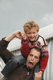 Family Fun. Kid (7) sitting on the shoulders of his favorite uncle making fun Royalty Free Stock Photography