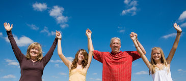 Family Fun Banner. Beautiful family holding hands and raising their arms against a blue sky Stock Photography