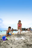 Family fun at beach. A brother and sister helping each other at making sand castle by the beach on tropical island holiday Stock Photography