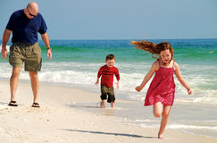 Family fun on the Beach. Father and children running and playing on pretty beach stock photo