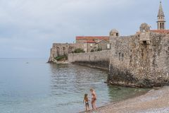 Family fun on a beach in Budva. Mother and daughter in swimming costumes playing on the beach on the Adriatic coast in spring, Budva, Montenegro Royalty Free Stock Images