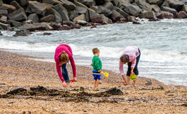 Family Fun on the Beach. Grandma, mum and a small child digging for treasure on the beach. A warm summer day out at the beach Royalty Free Stock Image