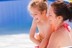 Family fun. Daughter and mother laughing together in the swimming pool Stock Photos