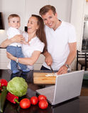 Family Fun in Kitchen. A happy mother and father with young toddler son,  having fun making food in the kitchen with online recipe Stock Images