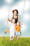 Family fun. Mom, daughter, son laughing on a swing Stock Photo