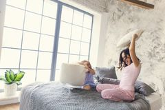 Family fun. Mother and daughter pillow fight stock image