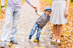 Family fun, mother, father and son holding hands. Family fun, happy mother, father and son holding hands in park and looking at camera Stock Images