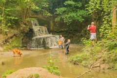 Family fun in a muddy pool near Burgess Hill, Sussex,England. Burgess Hill,Sussex,England 11 August 2017 A man photographs his children playing in a muddy Royalty Free Stock Photo