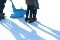 Family fun on outdoor ice rink, kid learning to skate with plastic seal as training aids. Family fun on outdoor ice rink with kids learning to skate with plastic stock photography