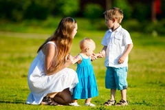 Family fun outdoors. Mother and two kids having fun outdoors at sunny summer day Stock Photos