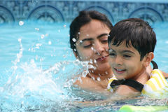 Family fun in the pool. Mother and son having a great time in the pool. Shallow DOF royalty free stock images