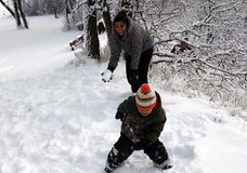 Family Fun with a snowball fight. First Nations, Indigenous mother and child having fun in a good old fashion Canadian winter snowball fight. Snow clinging to royalty free stock photos