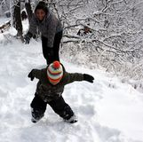 Family Fun with a snowball fight. First Nations, Indigenous mother and child having fun in a good old fashion Canadian winter snowball fight. Snow clinging to stock photos
