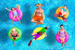 Family fun in the swimming pool in summer. With a father, mother, grandmother, boys and a girl floating on colorful inner tubes in their swimsuits in various Royalty Free Stock Images