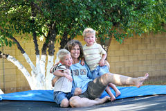 Family Fun on the Trampoline. A grandmother and 2 grandsons sit together on a backyard trampoline Stock Photos