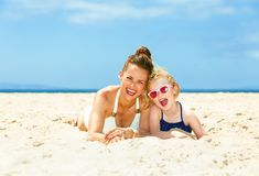 Happy young mother and child in swimsuit laying on seacoast. Family fun on white sand. Portrait of happy young mother and child in swimsuit laying on the stock photography