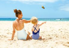 Modern mother and child on beach pointing at something. Family fun on white sand. Seen from behind modern mother and child in beachwear on the beach pointing at stock image