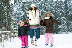 Family Fun in the Winter. A mother and two daughters jumping in the snow Stock Image