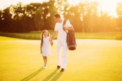 Family game of golf. Father and daughter are walking along the golf course taking their hands on the sunset Stock Images