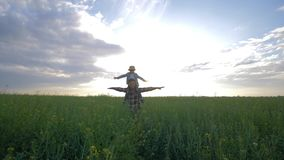 Family game, happy father wears his son on his shoulders during walk on rapeseed field on background sky and sunset. Family game, happy father wears his son on stock video