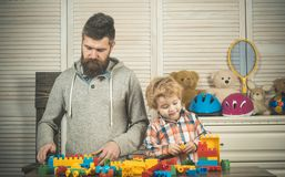 Family games concept. Family play with construction plastic blocks. Dad and kid with concentrated faces make brick constructions. Father and son play together royalty free stock images