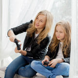 Family games. Mother and daughter play on conlsole together. Emotions. Family games. Mother and daughter play on colsole together Royalty Free Stock Photos