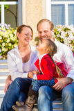 Family on garden bench in front of home Royalty Free Stock Image